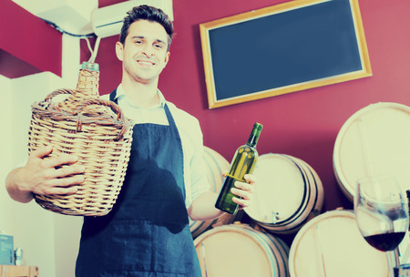 wicker work: Cheerful man seller in apron holding big wicker bottle with wine in store