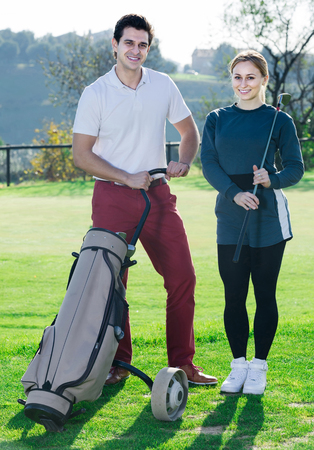 brassy: smiling american male and female golfers ready for team play at golf course