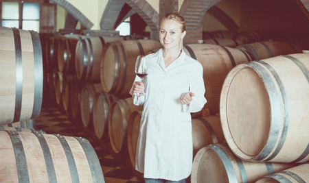 laboratorian: Cheerful female wine house worker checking quality of product in cellar