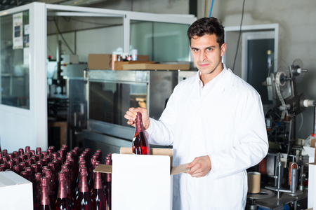 coveralls: smiling male employee in coat packing bottles into carton package on wine manufactory
