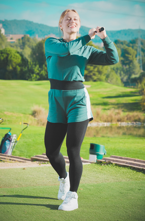 brassy: Adult girl is succeeded in ball hitting at golf course.