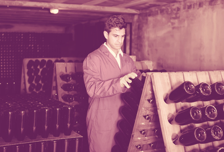 coveralls: man wearing uniform working with bottle storage racks in winery cellar