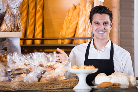 baker selling fresh pastry and baguettes in local bakery Imagens