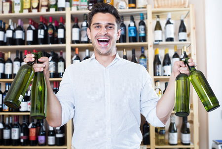 Cheerful man holding wine bottles in winery section in store