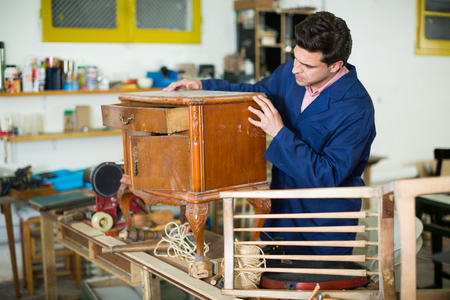 Man carpenter wearing blue overalls restoring furniture in restoration studio
