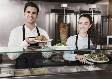 Portrait of happy workers with kebab at fastfood place