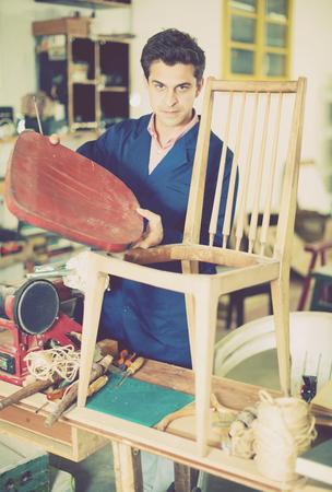 workroom: Man carpenter with screwdriver in hand working in furniture repair workshop