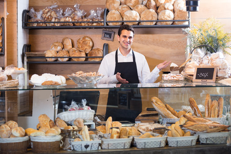 biscuits: portrait of man selling fresh pastry and baguettes in local bakery