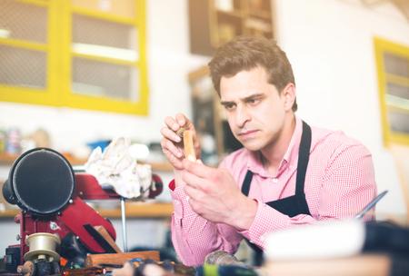 workroom: Portrait of serious craftsman in uniform working in carpentry Stock Photo