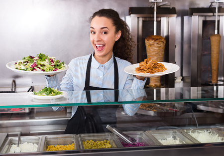 famous industries: Cheerful smiling female cook offering tasty kebab at bistro counter