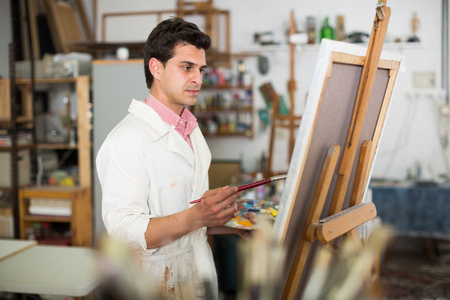 accurately: Creative male artist drawing picture with oil paints in studio