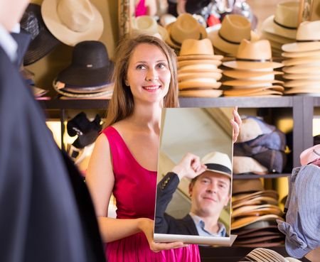 shopper: happy russian woman holding mirror and showing customer his reflection in hats shop Stock Photo