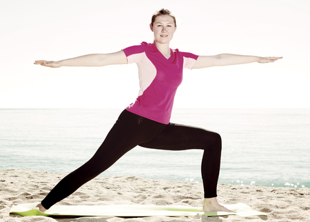 25s: Smiling young woman training yoga poses on beach in sunny morning Stock Photo