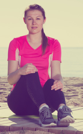 25s: Fitness woman relaxing after workout outdoors on background with smooth sea Stock Photo