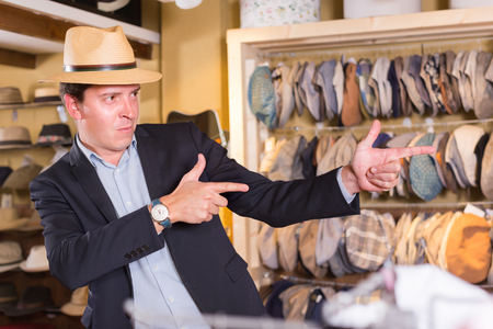 shopper: portret of smiling young french guy try on  panama at headwear store Stock Photo