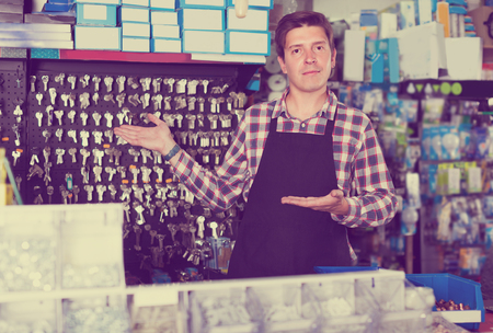 employe: Portrait of male seller which is selling and manufacturing keys in hardware store.
