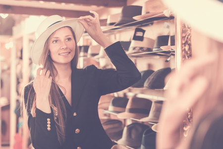shopper: female customer try on brim hat and looking in mirror at dressing room