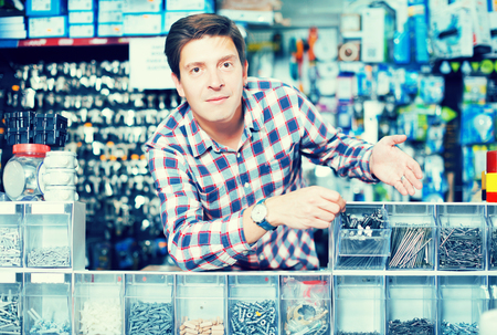 employe: Portrait of adult glad employee selling nuts, screw and fasteners in hardware store
