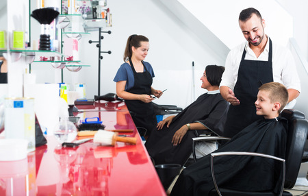 attentive: school boy sitting in chair in hairdresser salon and getting hair cut by joyful smiling  male hairdresser Stock Photo
