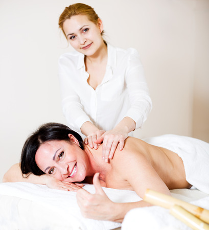 joyfulness: Positive young masseuse massaging shoulders and neck of adult woman in beauty parlor