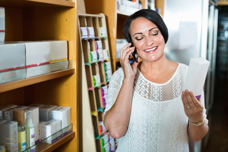 Charming smiling mature brunette woman chatting by phone while shopping in drugstore