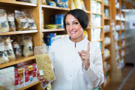 Portrait of young female pharmacist with wholegrain cereals and groats in hands