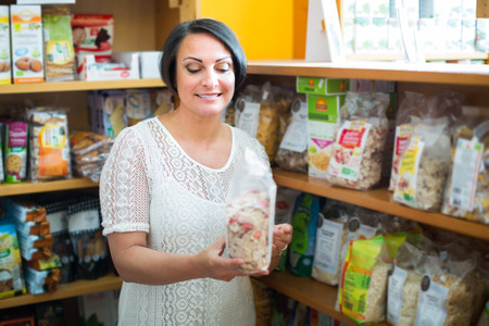 wholegrain: Positive mature female customer holding with cereal products in healthy food store
