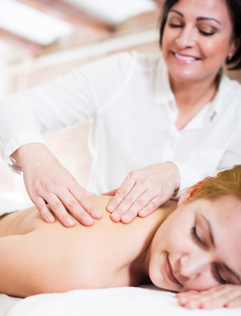 Smiling adult masseuse softly massaging shoulders and neck of young woman in massage salon. Selective focus on hands