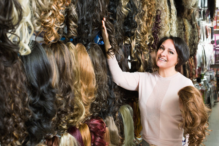 Positive charming smiling middle aged woman purchasing hair extension in salon