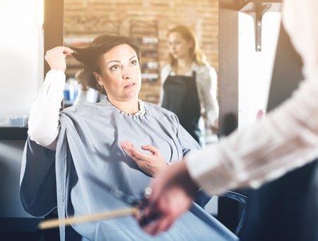 Adult woman is upset with work of young hair stylist and her hairdo in hairdress salon Stock Photo