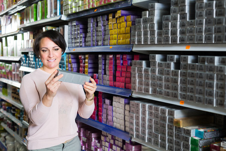 bleach: Positive young woman choosing box of hair dye in shop Stock Photo