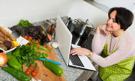 ensaladilla rusa: Smiling middle age housewife browsing internet for recipe in kitchen Foto de archivo