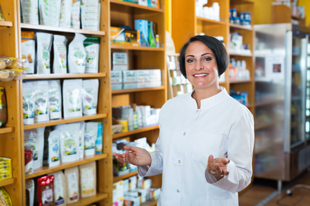 Happy  pleasant mature brunette woman in white coat promoting health supplements in drugstore Stock Photo - 80569424