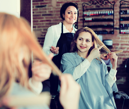 Smiling cheerful positive woman points to master in hairdress salon right hair length for haircut