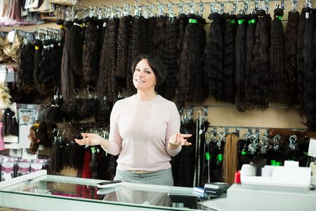 Laughing female assistant selling natural hail ponytails, tresses and wigs