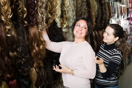 additional: Purchasers buying clip-in natural hair extension at store Stock Photo