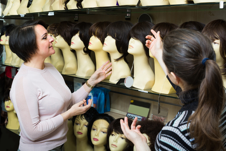 peruke: Female buyers discussing synthetic and natural hair perukes at store together
