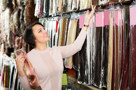 Cheerful female customer selecting clip-in hair extension at store Stock Photo