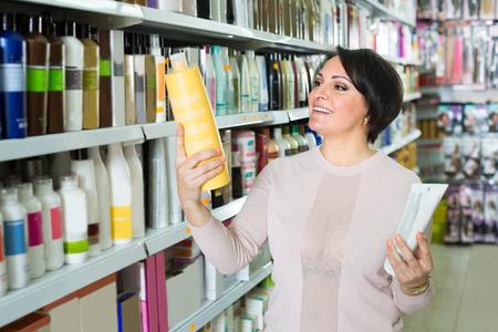 shopper: Elegant female customer buying conditioner for hair  indoors