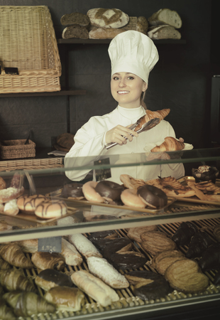 potěšen: Joyful  smiling  young female baker offering pastry in the confectionery shop