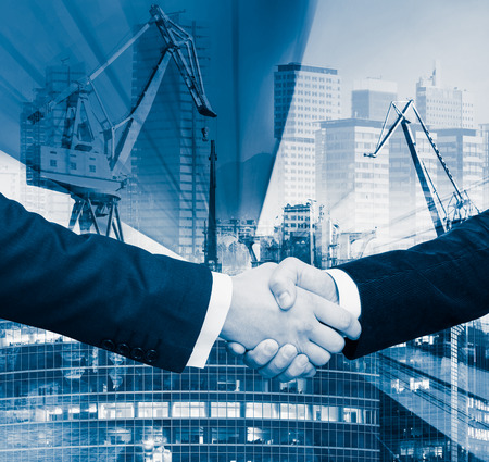 Business handshake on background of construction crane in rays of light