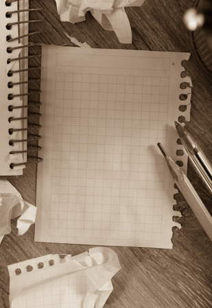 writing utensil: Empty crumpled pages from notebook lying on wooden surface