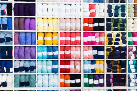 Estantes con varios hilos de tejer en taller de costura. Foto de archivo