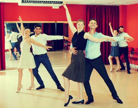 Jonge lachende mensen die gepassioneerde samba in dansklasse oefenen Stockfoto