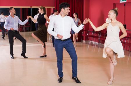 Jonge lachende mensen die krachtige jivebewegingen in dansklasse oefenen