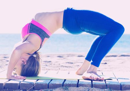 athleticism: Portrait of active sportswoman exercising practice of yoga on the beach Stock Photo
