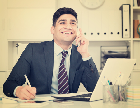 expertize: Man is discussing the contract by phone in the office.