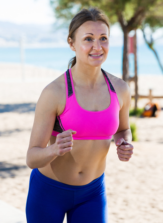 Happy adult woman practicing jogging for warm-up body in nature
