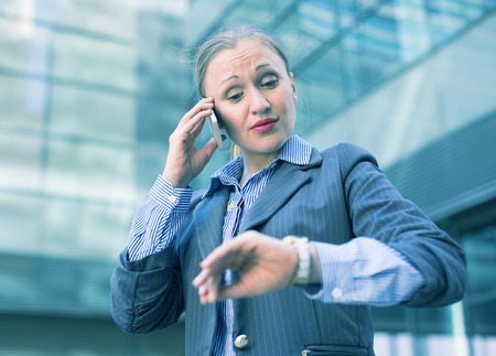 Businesswoman hurrying to meeting and watching on wristwatch outdoors Stock Photo