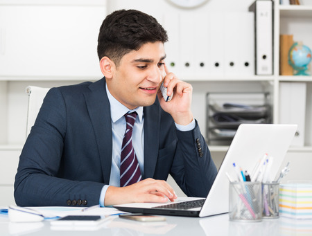 expertize: Young man is working at a computer and talking phone in the office.